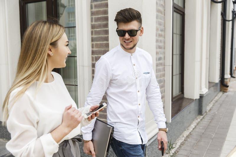 Les beaux couples marchent ensemble sur la rue Ils regardent l'un l'autre Le type sourit un peu image stock