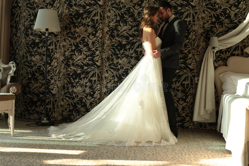 Les beaux couples, marié et jeune mariée portent des vêtements de mariage, embrassant dans la chambre à coucher photo stock
