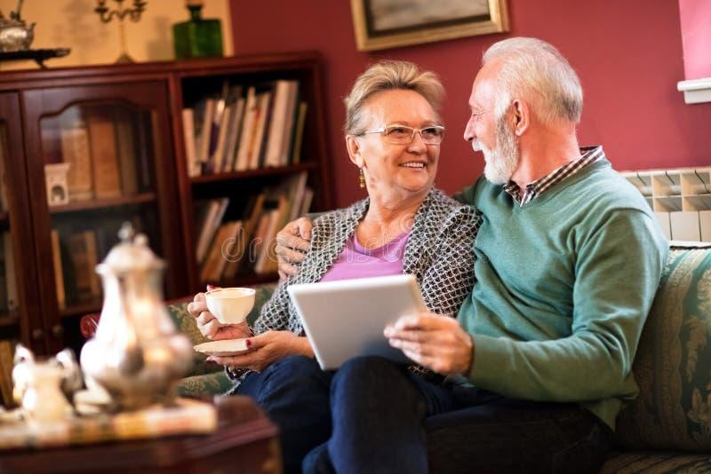 Les beaux couples supérieurs apprécient à la maison tout en parlant et buvant le te photo libre de droits