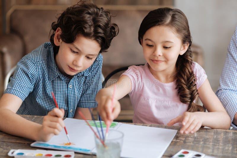 Les beaux enfants gais peignant une aquarelle décrivent ensemble image stock