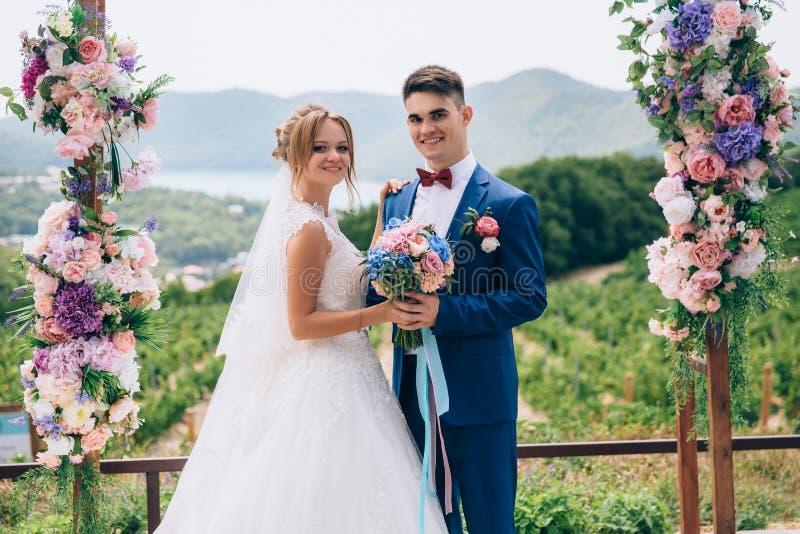 Les beaux et souriants jeunes posent sous une voûte de fleur parmi une nature magnifique Une fille dans une robe de mariage photographie stock