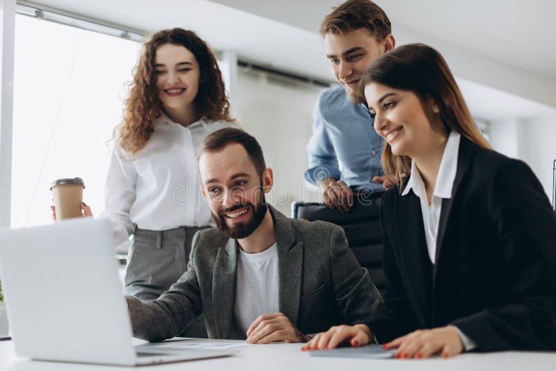 Les beaux gens d'affaires utilisent des ordinateurs et sourient tout en travaillant dans le bureau image stock