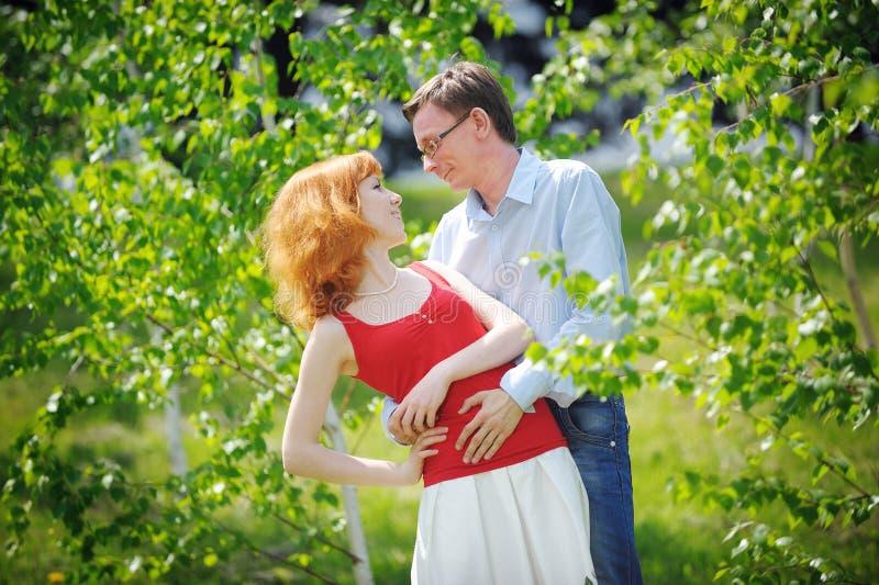 Les beaux jeunes couples affectueux embrassant en ressort de fleur font du jardinage images libres de droits
