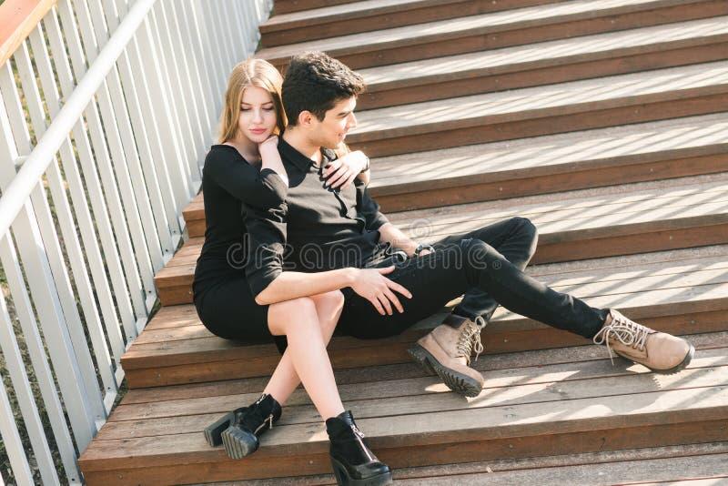 Les beaux jeunes couples multiraciaux, couples d'?tudiant dans l'amour, reposent l'escalier en bois dans la ville Belle ?treinte  image stock