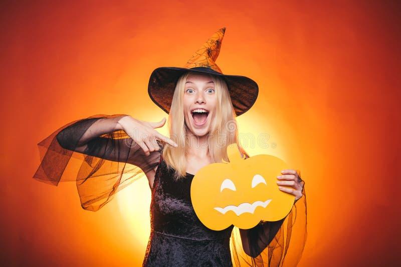 Les beaux jeunes ont étonné la femme dans les sorcières chapeau et costume dirigeant la main - représentation des produits Mode d images stock