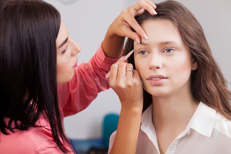 Les beaux modèles dans le salon de beauté, faire d'artiste de maquillage font photos libres de droits