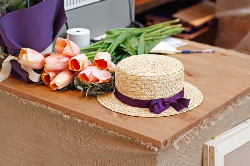 Les beaux tulipes et chapeau se trouvent sur la table en bois image stock