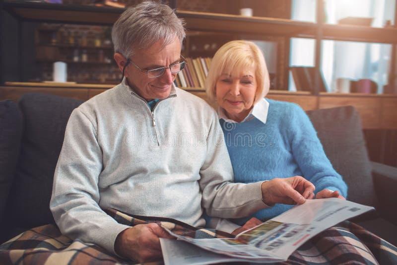 Les beaux vieux couples se reposent sur le divan ensemble et le readi photos stock