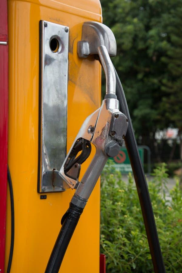 Les becs de pompe à gaz dans la rétro station service images libres de droits
