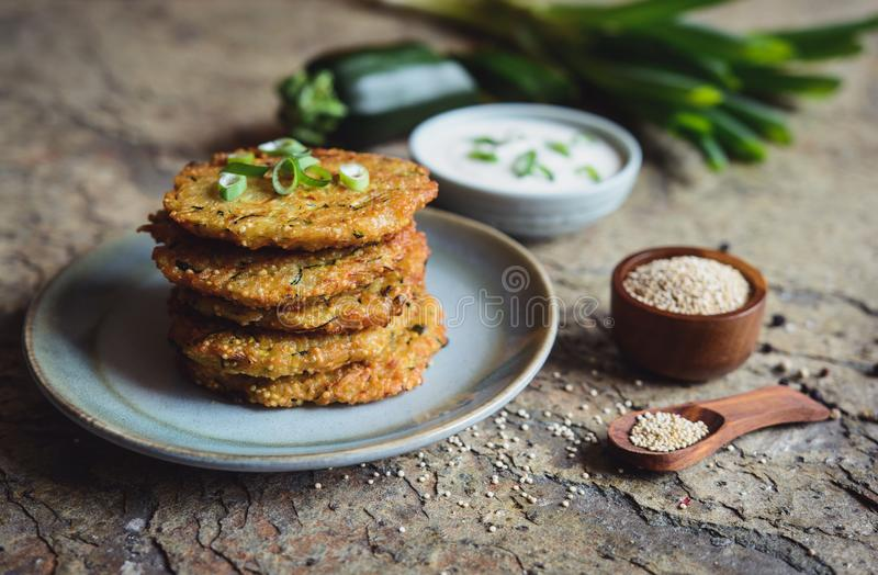 Les beignets de quinoa avec la courgette, l'ail et l'oignon vert ont servi avec l'immersion de yaourt images libres de droits