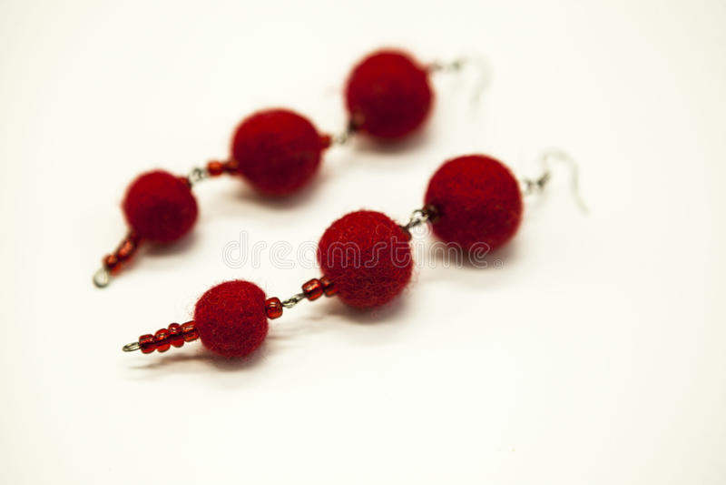 Les belles boucles d'oreille fabriquées à la main felted les nuances rouges de moutons de laine sur un fond blanc, plan rapproché images stock