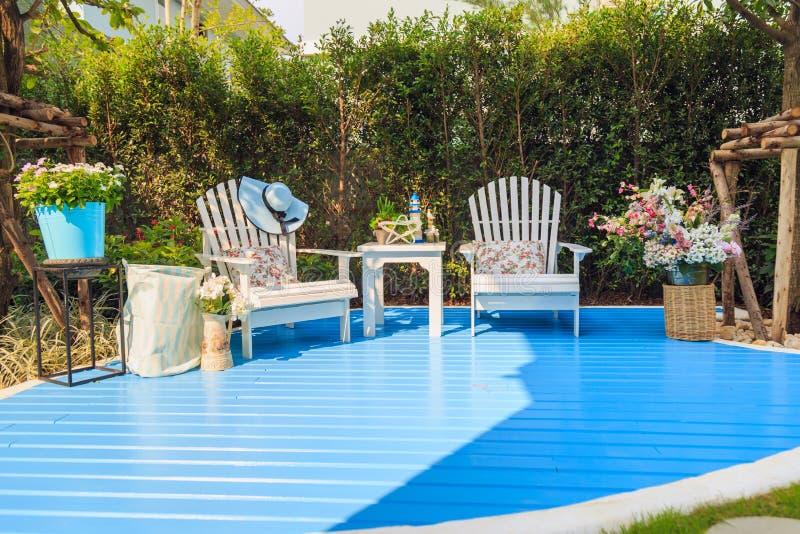 Les belles chaises en bois blanches et la table en bois sur bleu-clair courtisent photographie stock