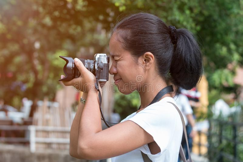 Les belles femmes asiatiques avec le sac ? dos visent l'appareil-photo dans la jungle image libre de droits