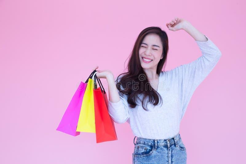 Les belles femmes asiatiques heureuses ont plaisir à faire des emplettes sur le fond rose, Shopaholic, achat pendant la promotion photos libres de droits