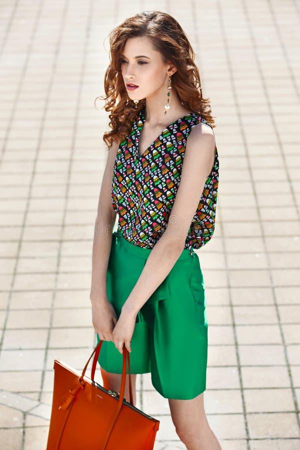Les belles femmes habillées dans des shorts verts élégants et un sac orange de participation supérieure lumineuse marche dans la  photo libre de droits