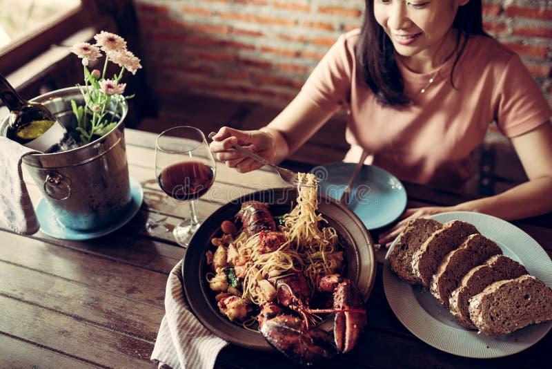 Les belles femmes mangent le homard un sourire de fiasco photo stock
