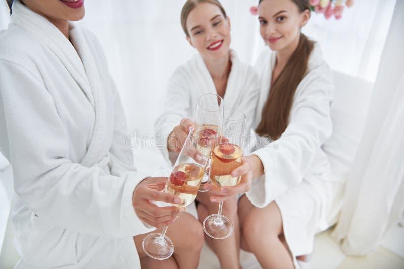 Les belles filles avec de l'alcool boit au salon de station thermale photos libres de droits