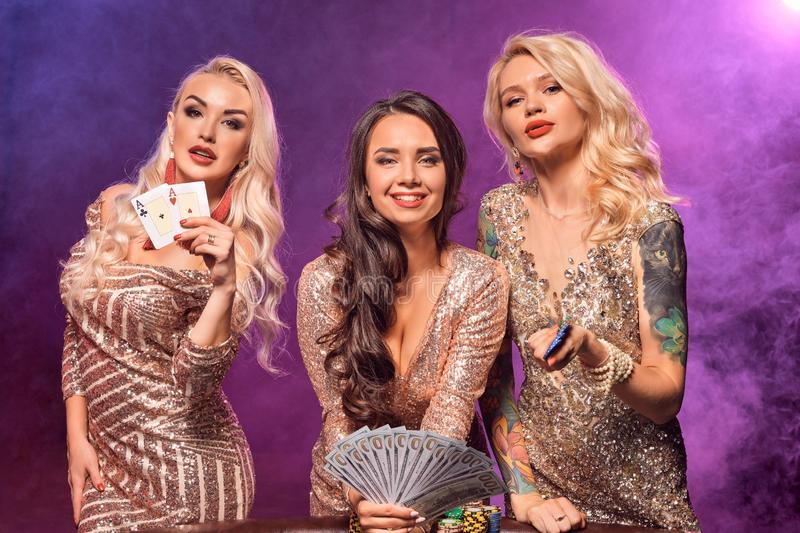 Les belles filles avec des coiffures parfaites et maquillage lumineux posent la position à une table de jeu Casino, tisonnier images stock