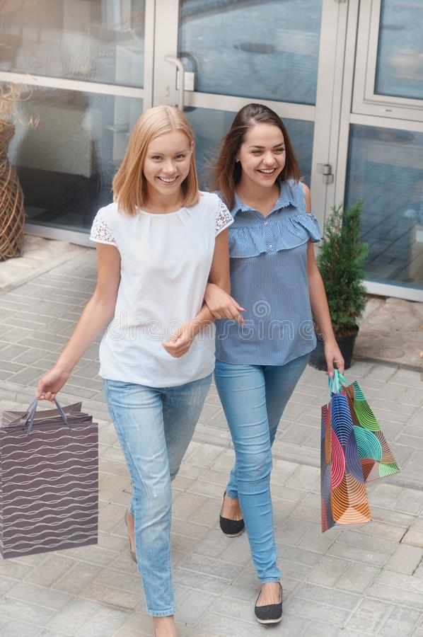 Les belles filles avec des paniers marchent par la ville photo libre de droits