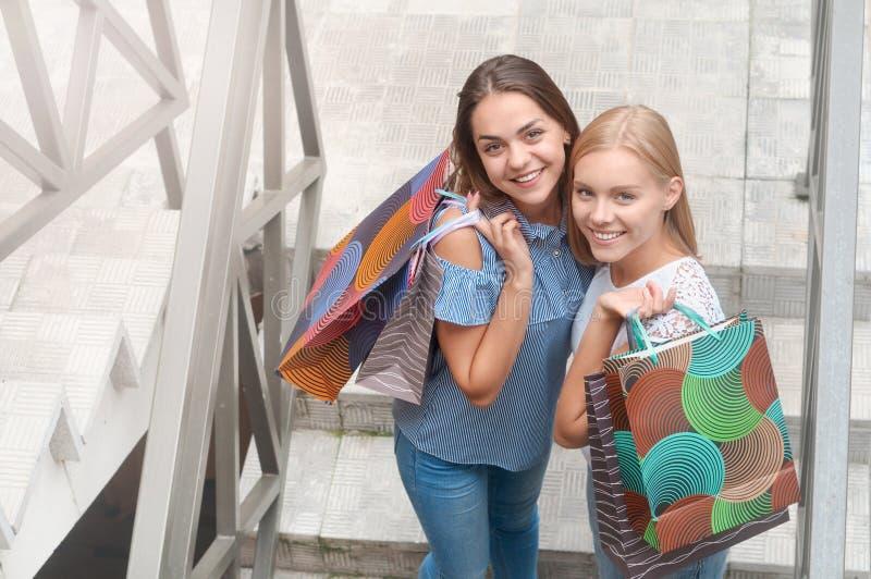 Les belles filles avec des sacs à provisions se tiennent sur des escaliers images stock