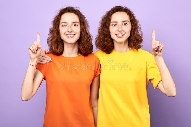 Les belles filles heureuses de jumeaux se dirigent vers le haut de d'isolement sur le fond bleu photos stock