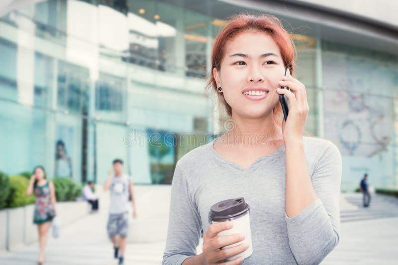 Les belles jeunes femmes appellent le téléphone et tiennent la tasse de café photos stock