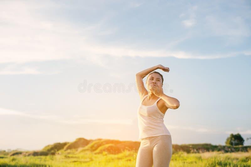 Les belles jeunes femmes de yoga étirent sa main et le baîllement en m photos libres de droits
