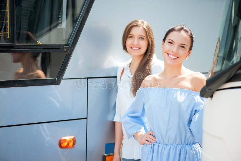 Les belles jeunes filles attendent l'autobus photos stock