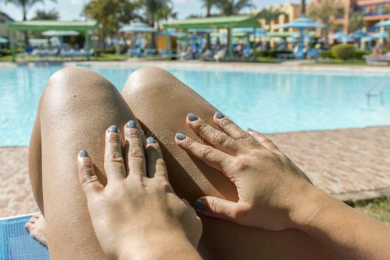 Les belles jeunes jambes minces de femme les prennent un bain de soleil près de la piscine Fille prenant un bain de soleil par la photos stock