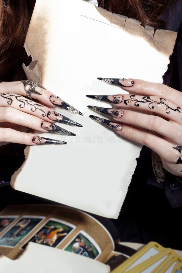 Les belles mains avec la longue sorcière acrylique noircissent des clous tenant une feuille blanche dans les mains de photographie stock libre de droits