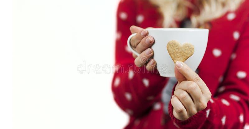 Les belles mains douces de fille tiennent les biscuits en forme de coeur de Noël doux savoureux lumineux avec une tasse de thé photo libre de droits