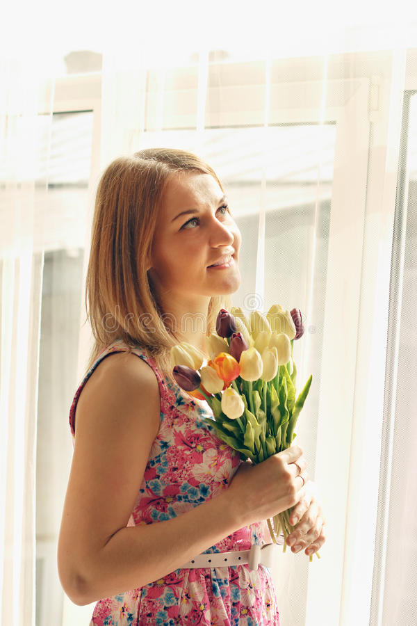 Les belles tulipes de sourire de femme se tient près de la grande fenêtre image stock