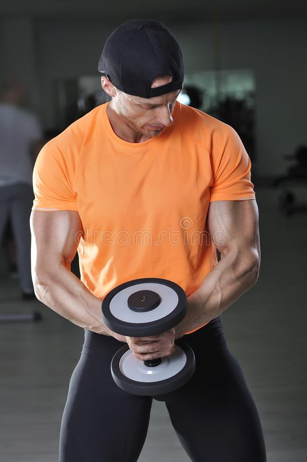 Les biceps de exécution d'homme sportif puissant bel s'exercent avec l'haltère images stock