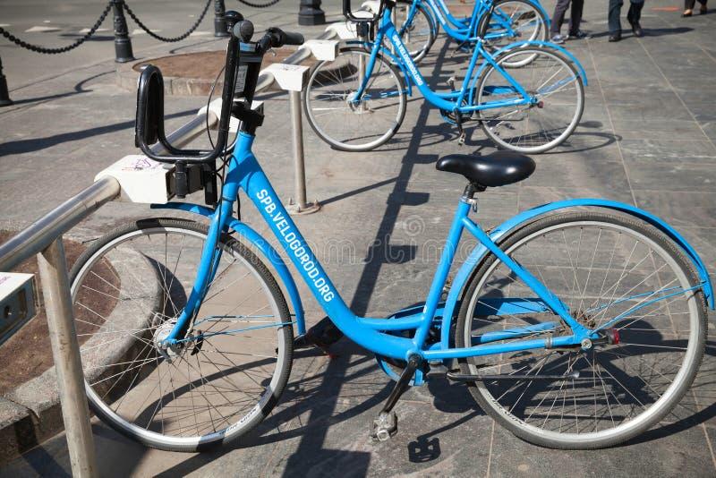 Les bicyclettes bleues modernes de ville pour le loyer se tiennent sur un stationnement photos libres de droits