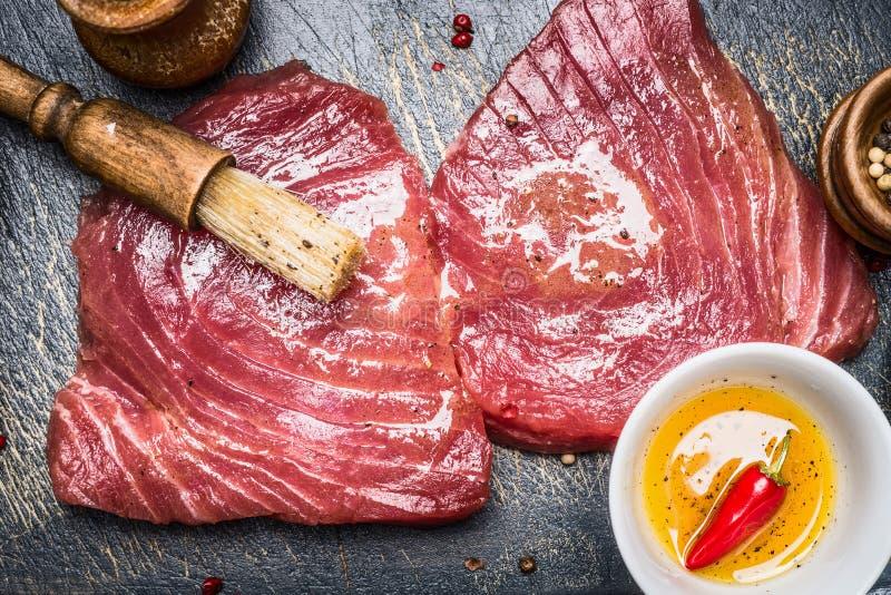 Les biftecks de thon crus marinant pour le gril ou faisant cuire avec la brosse et les épices huile, vue supérieure photo libre de droits