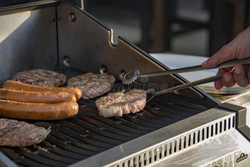 Les biftecks juteux brûlés de basculement ou brûlants grésillent sur le gril flamboyant et fumant images stock