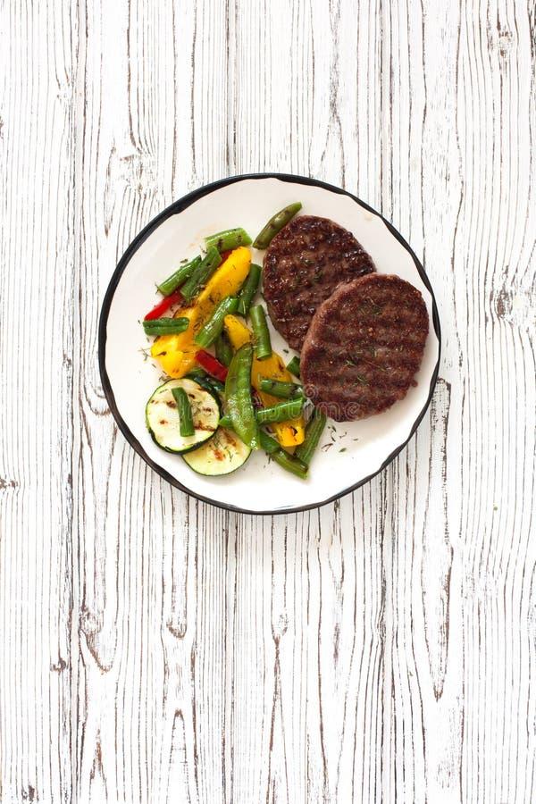 Les bifteks ont grillé avec des légumes dans le plat blanc sur un blanc courtisent photo libre de droits