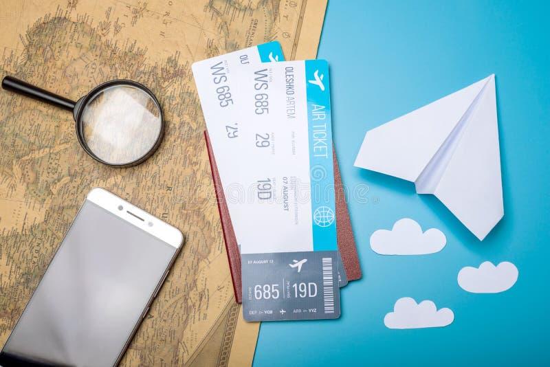 Les billets d'avion avec le passeport et le papier surfacent sur le fond de carte du monde, topview Le concept des transports aér image libre de droits