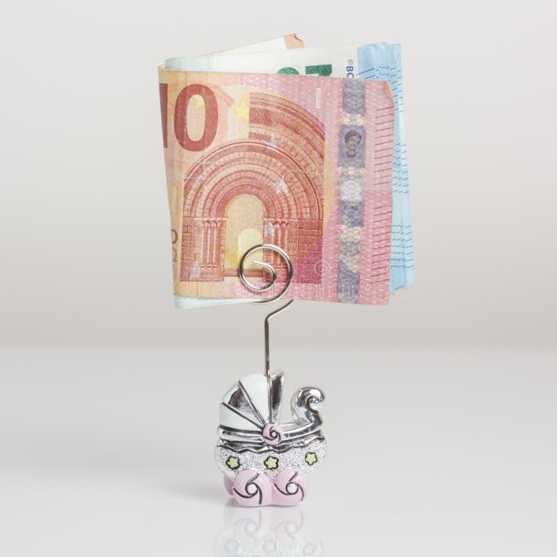 Les billets de banque se sont pliés dans une poussette formée épousant la faveur sur un fond blanc image libre de droits