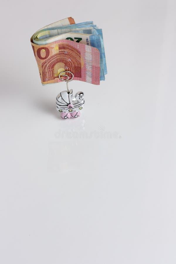Les billets de banque se sont pliés dans une poussette formée épousant la faveur sur un fond blanc photo stock
