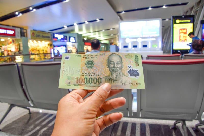 Les billets de banque vietnamiens sont aux mains des hommes sur le fond d'aéroport à Hanoï, Vietnam image stock