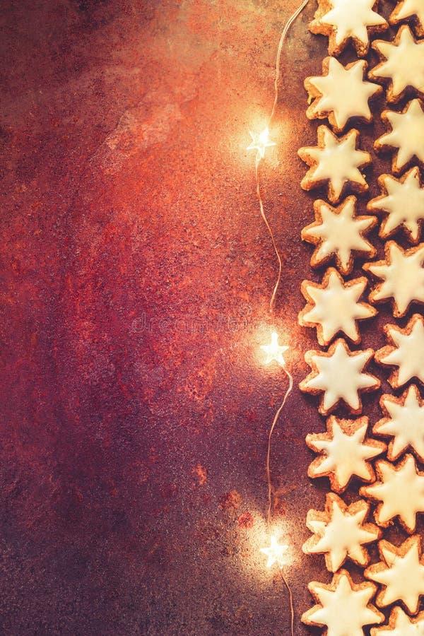 Les biscuits allemands de Noël autoguident les étoiles vitrées cuites au four de cannelle avec le scintillement Nuts Garland Ligh photo libre de droits