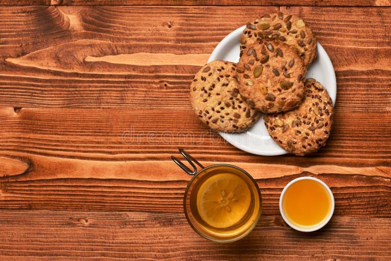 Les biscuits avec des graines ont placé près de la tasse de thé et de miel photos stock