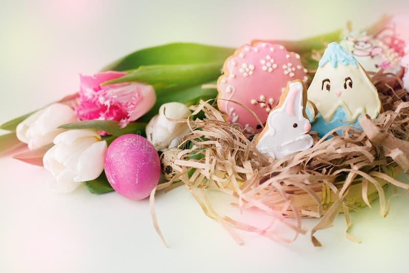 Les biscuits colorés de Pâques avec givrer le décor de glaçage, ont peint les oeufs et les tulipes colorés sur la table légère Co image libre de droits
