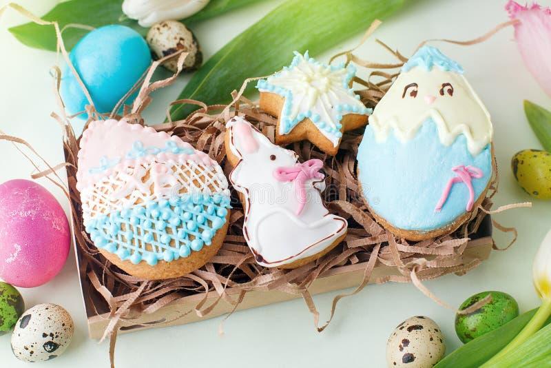 Les biscuits colorés de Pâques avec givrer le décor de glaçage, ont peint les oeufs et les tulipes colorés sur la table légère Co photos libres de droits