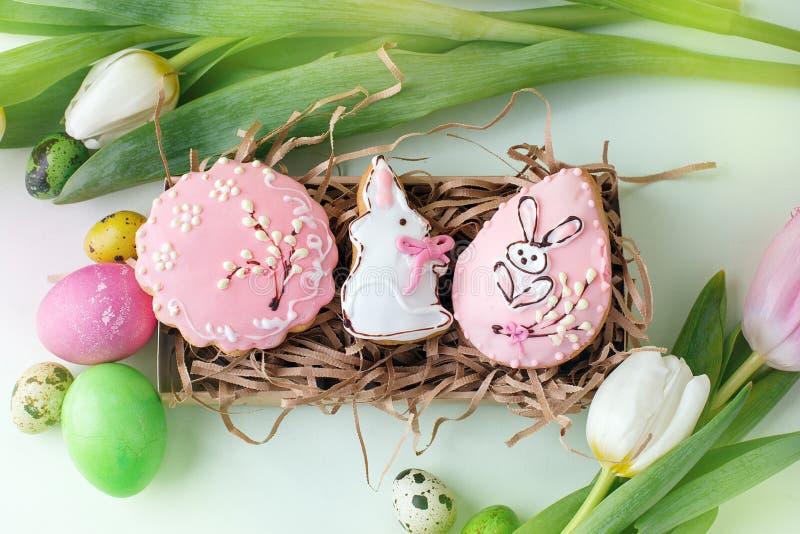 Les biscuits colorés de Pâques avec givrer le décor de glaçage, ont peint les oeufs et les tulipes colorés sur la table légère Co photo libre de droits