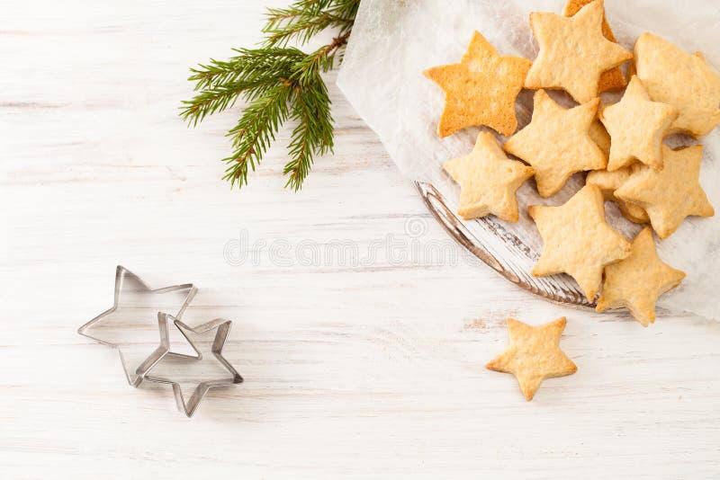 Les biscuits cuits au four frais sur le papier de cuisson avec le sapin s'embranchent sur le blanc photo stock