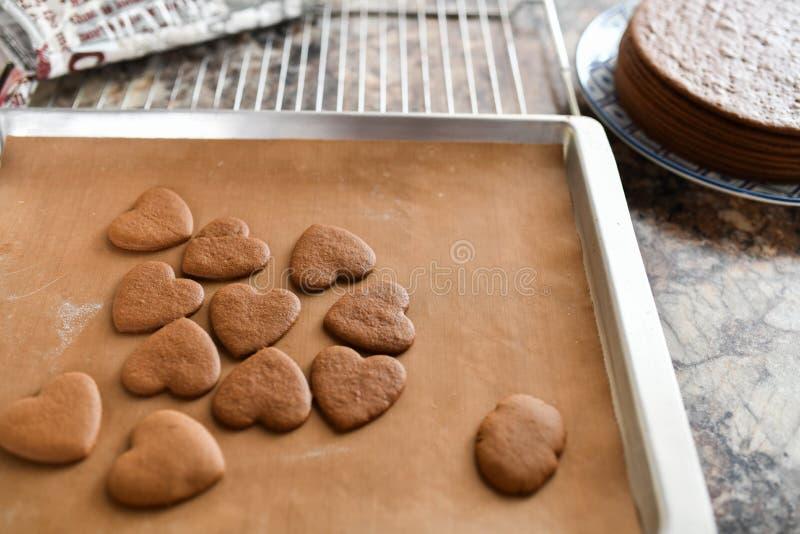 Les biscuits de chocolat sur une plaque de cuisson, les biscuits en forme de coeur ont fait cuire à la maison image stock