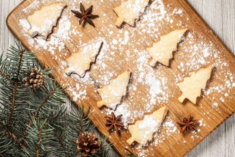 Les biscuits de pain d'épice dans l'arbre de Noël forment sur le spri de conseil en bois photo stock