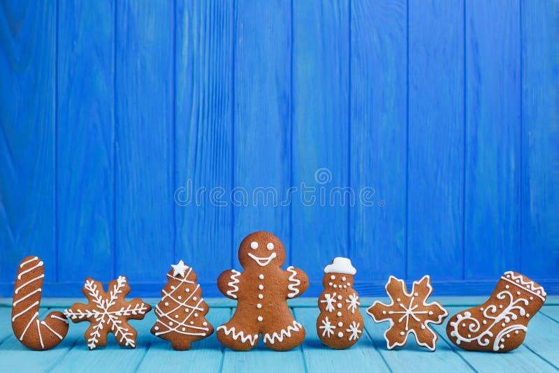 Les biscuits de pain d'épice de Noël ont placé sur le fond bleu lumineux avec images libres de droits